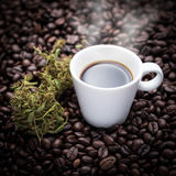 Cannabis coffee cup. A cup of hot espresso as beside cannabis buds also see many roasted coffee beans on a floor Royalty Free Stock Photos