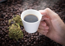 Cannabis coffee. Hand grabbing an ear cup of hot espresso as beside cannabis buds also see many roasted coffee beans on a floor Stock Photos