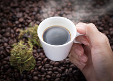 Cannabis coffee. Hand grabbing an ear cup of hot espresso as beside cannabis buds also see many roasted coffee beans on a floor Royalty Free Stock Photos