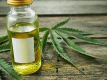 Cannabis com óleo do extrato em uma garrafa imagens de stock royalty free