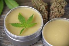 Cannabis hemp cream with marijuana leaf and nug on wood surface stock photos