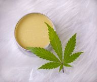 Cannabis hemp cream with marijuana leaf over white background stock photography