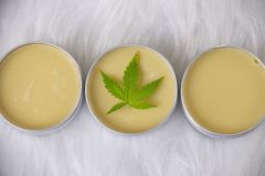 Cannabis hemp creams with marijuana leaf over white. Background - topicals concept royalty free stock photo