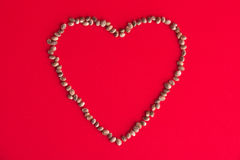 Cannabis & x28;hemp& x29; seeds forming a heart over red background - medi Stock Image