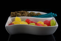 Cannabis infused caramels in different colors and dry marijuana Royalty Free Stock Photo