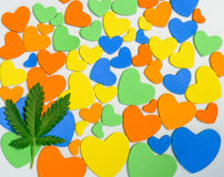 Cannabis lies on a background of colorful hearts. Stock Photo