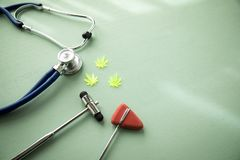 Cannabis marijuana hemp CBD as pain killer or medical therapy at neurologist doctors office with reflex hammer and stethoscope stock photo
