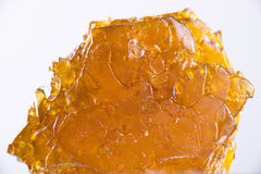 Cannabis oil concentrate aka shatter isolated over white backgro. Big piece of cannabis oil concentrate aka shatter isolated over white background Stock Photography