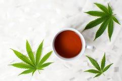 Cannabis tea and marijuana leaves on white fabric stock images