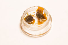 Cannabis Wax. A small quantity of cannabis wax in a clear plastic container Stock Images