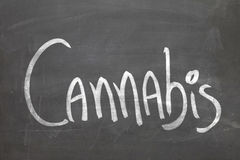 Cannabis word in white chalk handwriting on the blackboard Royalty Free Stock Photography