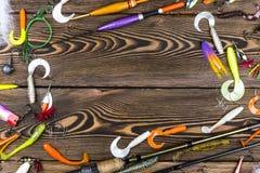 Canne à pêche, attirail et appâts, bobine sur le fond de conseil en bois Photographie stock