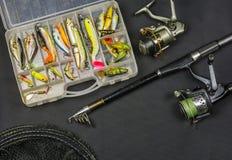 Canne à pêche avec la bobine, ensemble d'amorces artificielles et filet de pêche Image stock
