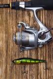 Canne à pêche avec la bobine et attirail pour pêcher sur le fond du plan rapproché foncé de conseils photo libre de droits