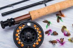 Canne à pêche avec la bobine et attirail pour pêcher sur un fond clair de la table photo stock