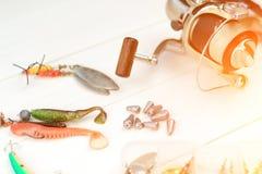Canne à pêche avec la bobine, les cuillers, l'attirail et les wobblers dans la boîte pour pêcher ou pêcher un poisson prédateur s Photos stock