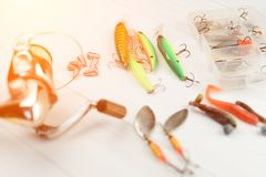 Canne à pêche avec la bobine, les cuillers, l'attirail et les wobblers dans la boîte pour pêcher ou pêcher un poisson prédateur s Image stock