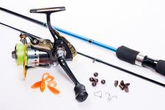 Canne à pêche et bobine avec des amorces de silicone sur le blanc Photo stock