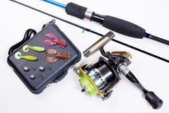 Canne à pêche et bobine avec la boîte pour des amorces sur le blanc Photo stock
