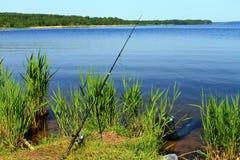 Canne à pêche et ragoût sur le côté du fleuve Photo stock