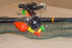 Canne à pêche et spinnings dans la composition avec des accessoires pour pêcher sur le fond sur la table Photographie stock libre de droits