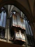 Canne d'organo della chiesa contro una finestra ovale fotografia stock