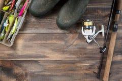 Canne da pesca e bobina con gli stivali e le attrezzature di pesca in una scatola su fondo di legno con spazio libero Fotografia Stock Libera da Diritti