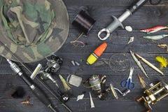 Canne da pesca e bobine, attrezzatura di pesca su backgroun di legno nero Immagine Stock