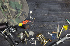 Canne da pesca e bobine, attrezzatura di pesca su backgroun di legno nero Fotografia Stock