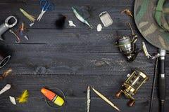 Canne da pesca e bobine, attrezzatura di pesca su backgroun di legno nero Fotografie Stock Libere da Diritti