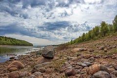 Canne da pesca nella composizione con una pietra al fiume di Varzuga sotto un bello cielo nuvoloso Immagine Stock