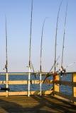 Canne da pesca sul pilastro dell'oceano Fotografia Stock Libera da Diritti