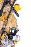 Canne da pesca sulle pietre con l'ancora e le foglie Fotografia Stock