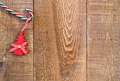 Canne de sucrerie avec l'arbre de Noël en bois accrochant de vintage sur rustique Photo libre de droits