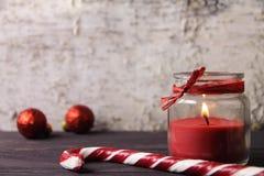 Canne de sucrerie, bougie sur un fond en bois Photos stock