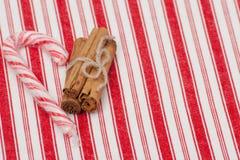 Canne de sucrerie de Noël Cannelle entière Sur le rouge image stock