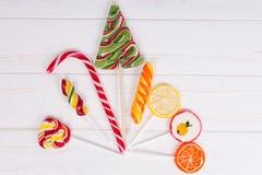 Canne de sucrerie et différentes lucettes lumineuses colorées comme fruits et Photo stock