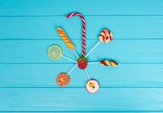Canne de sucrerie et lucettes comme orange et citron sur la turquoise en bois Photo stock