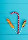Canne de sucrerie savoureuse et lucettes lumineuses colorées sur le verrat de turquoise Photographie stock libre de droits