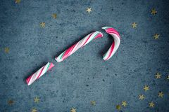 Canne de sucrerie sur le fond concret gris avec les étoiles d'or Fond de Noël Photographie stock