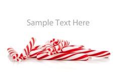 Canne di caramella rosse e bianche su bianco con lo spazio della copia Immagini Stock