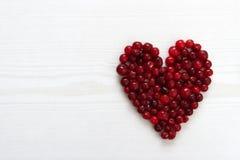 Canneberges dans la forme de coeur sur le conseil en bois Photos libres de droits