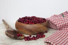 Canneberges de baies dans un plat fait main en bois Image libre de droits