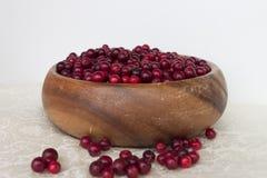Canneberges de baies dans un plat fait main en bois Photo libre de droits