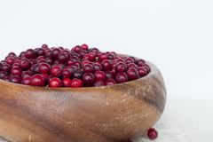 Canneberges de baies dans un plat fait main en bois Photographie stock libre de droits