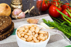 Canned beans with olive oil and garlic in white salad bowl. Studio Photo Stock Images