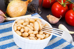 Canned beans with olive oil and garlic in white salad bowl. Studio Photo Royalty Free Stock Image