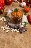 Canned beans with vegetables. In tomato sauce on wooden background. Selective focus Royalty Free Stock Image