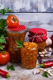 Canned beans with vegetables. In tomato sauce on wooden background. Selective focus Stock Photos