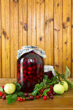 Canned cherries. Vessel unto three liters and had a jar canned cherries and apples, red currantagainst the background wooden boards Royalty Free Stock Image